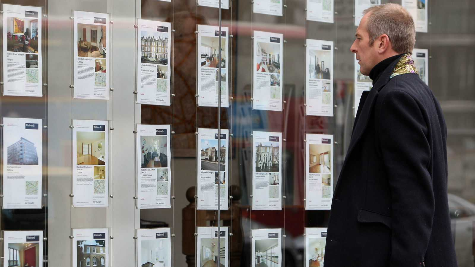A man looking into an estate agent s window